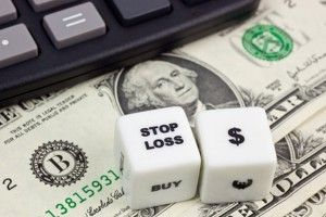US currency with calculator and dice showing STOP LOSS
